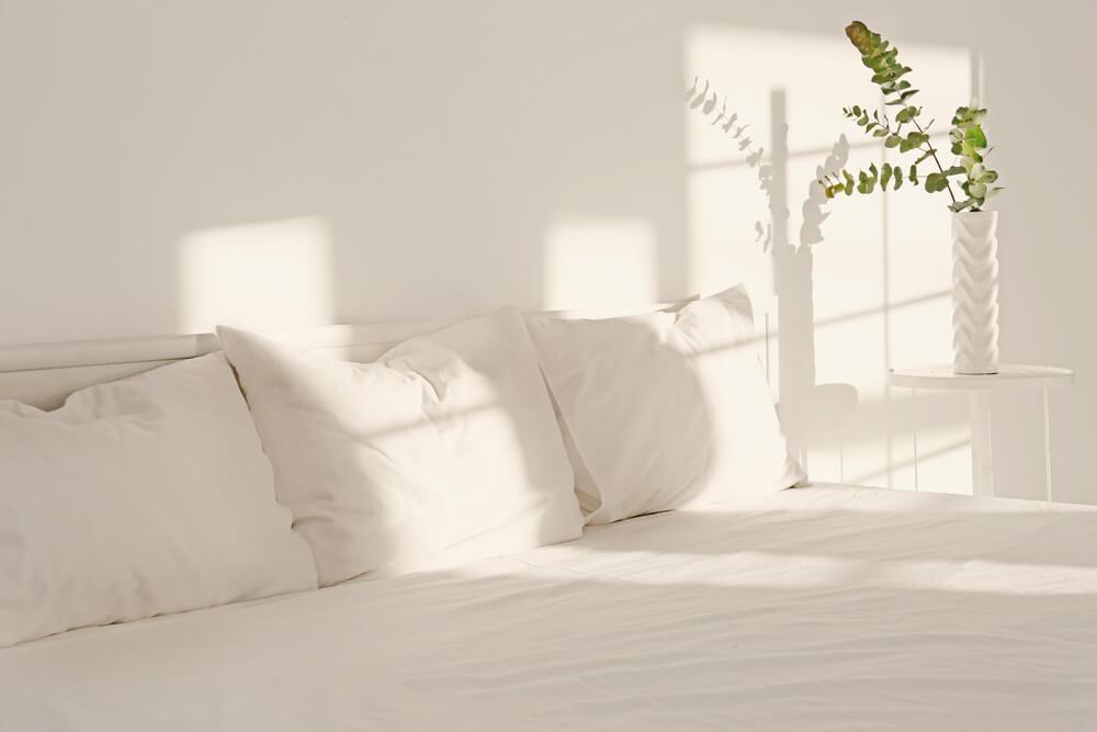 Imagem de uma cama recebendo iluminação indireta do sol.