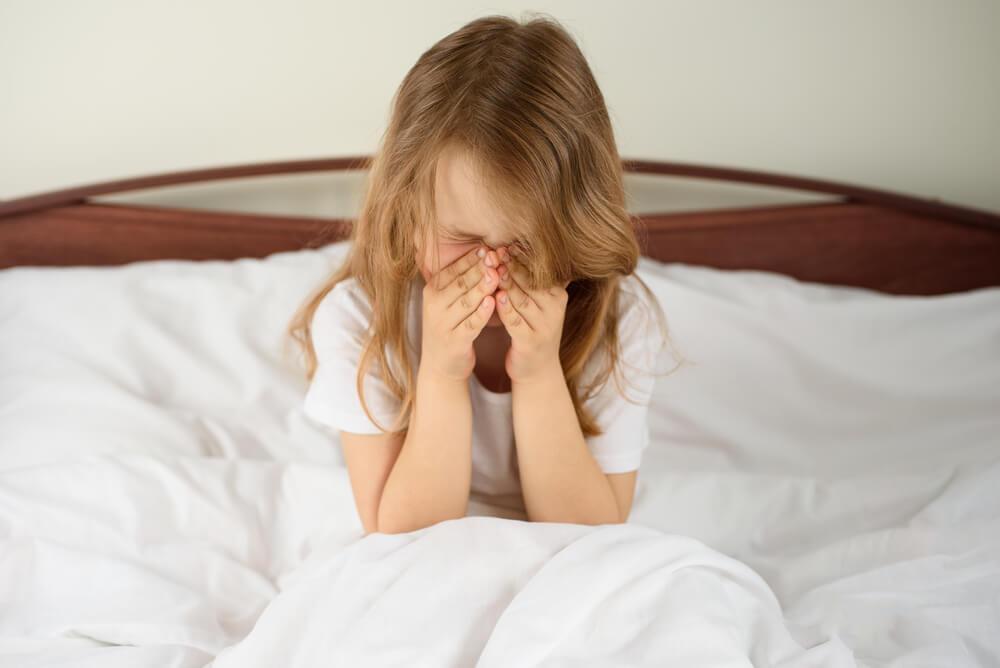Menina sentada em uma cama, enquanto coça o nariz por causa de uma alergia.