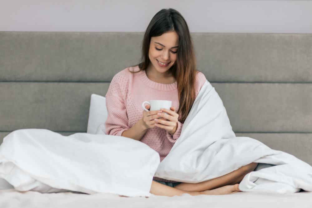 Mulher sentada em uma cama, enquanto toma um chá antes de dormir.