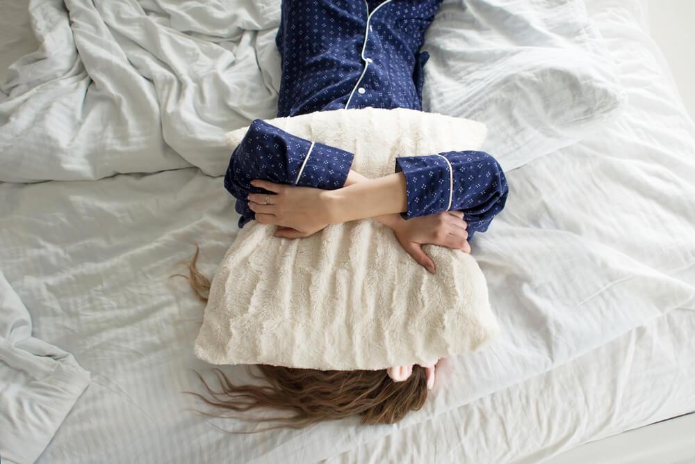 Mulher deitada em uma cama, abraçando o travesseiro e escondendo o rosto com ele.