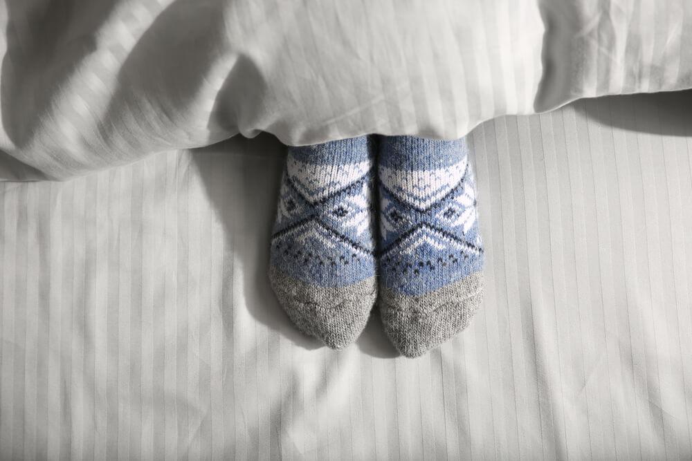 Foto de pés usando meias antes de dormir.