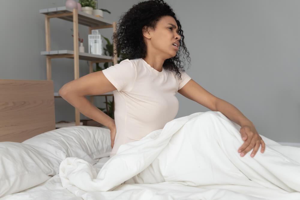 Mulher negra sentada em uma cama. Ela aparenta estar com dor nas costas, pois dormiu de mal jeito.