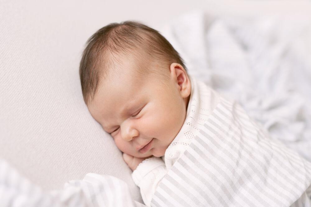 Bebê dormindo em fase de sono profundo, enquanto sorri.