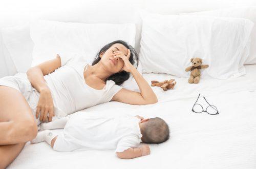 Uma mãe com sono, deitada em uma cama, ao lado de um bebê.
