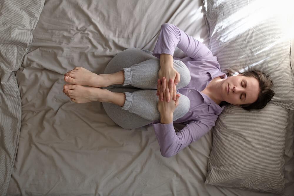 Mulher fazendo a posição de yoga Apanasana, capaz de aliviar dores lombares.
