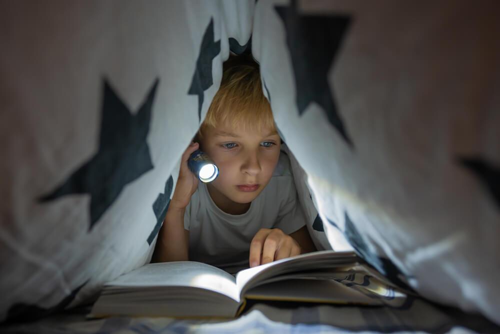 Criança deitada em uma cabana de lençol, segurando uma lanterna que está iluminando um livro.