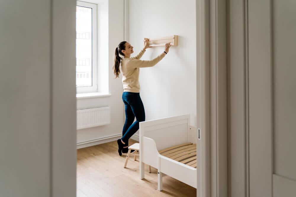 Mulher reformando o quarto gastando pouco. Ela está pregando algo na parede.