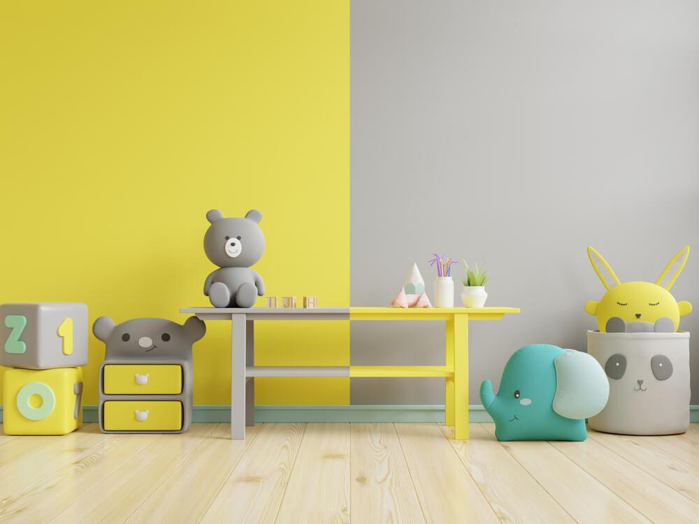 Imagem de da parede de um quarto de criança. Metade dela está pintada de cinza, enquanto a outra metade está pintada de amarelo.