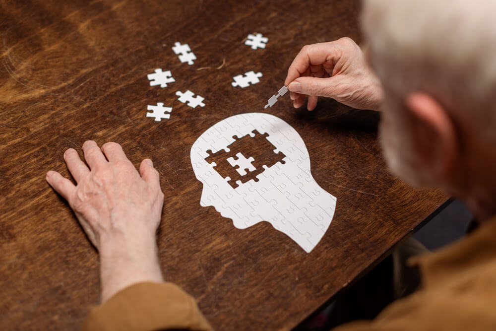 Imagem de um senhor sentado em uma mesa. Ele está montando um quebra-cabeça que tem formato de tronco humano. No cérebro, está faltando uma peça.