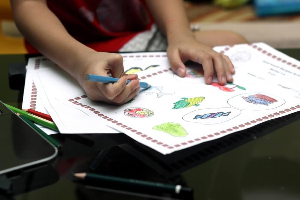 Imagem de uma criança fazendo desenhos coloridos.